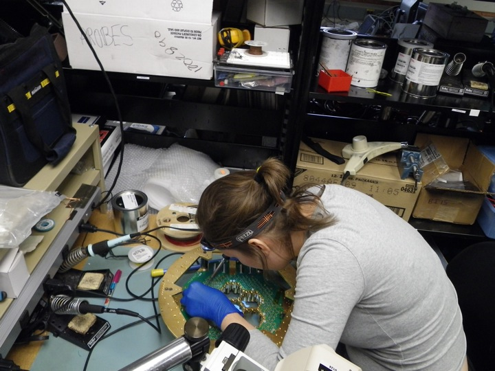 Abby Crites touching up solder joints on the PCB board connecting to the 90 GHz pixels.