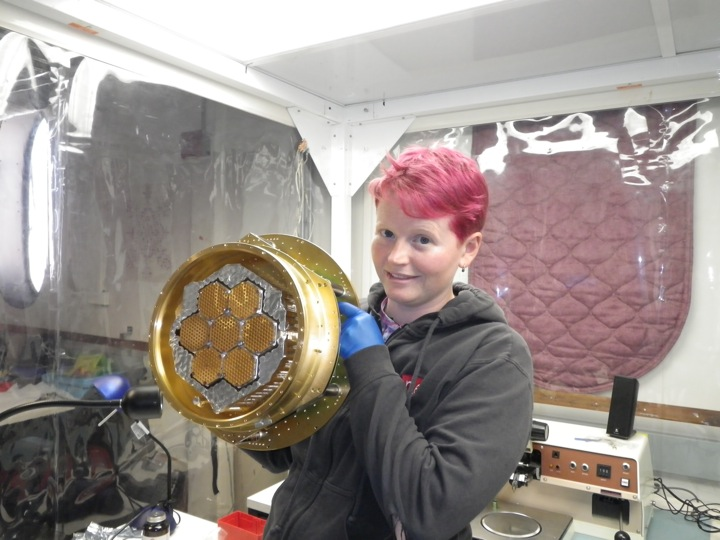 Liz George holding the partially assembled focal plane. The 150 GHz horns are open, while the feedhorns on the 90 GHz pixels are covered in aluminum tape.